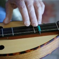 Closeup of Hennessy dulcimer with interesting capo design